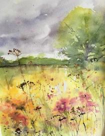 Meadow flowers and grasses with bank of distant trees and large tree