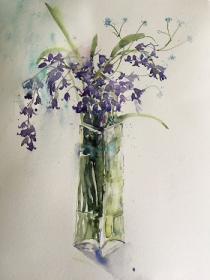 Bluebells with forget me nots in a tall glass vase.
