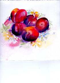 Five brightly coloured plums on a flower decorated plate