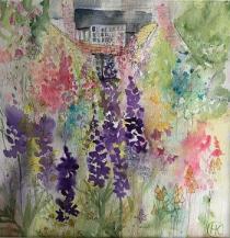 A manor house viewed through a  mass of summer cottage garden flowers
